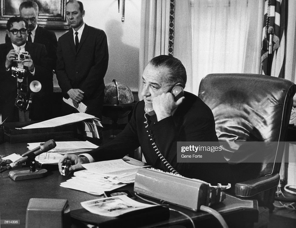 In his Washington office, US president Lyndon B. Johnson (1908 - 1973) congratulates astronauts Virgil Grissom and John Young after their triple orbit of the Earth, 1965.