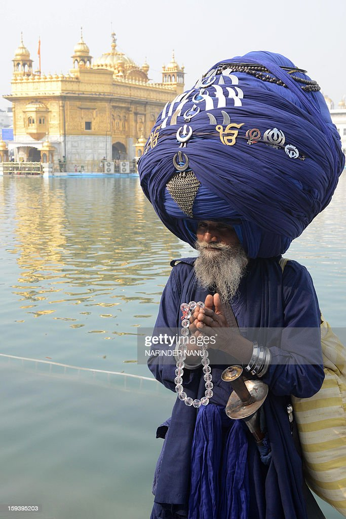 In Indian member of the Sikh Nihang Army, a traditional Sikh religious warrior, wearing a turban of over 300 metres in length poses for a photo during the Maghi Mela festival at the Sikh Shrine Golden Temple in Amritsar on January 13, 2013. Maghi Mela follows the Lohri or harvest festival and commemorates fighters in the Battle of Khidrana fought between Mughal army and the 10th Sikh Guru, Gobind Singh Ji.