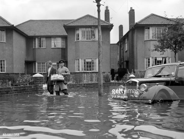 In knee deep flood water a milkman goes on his rounds in Berkely Close Ruislip Middlesex