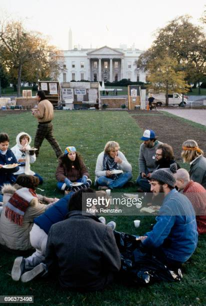 In Lafayette Park a group of people sit in a circle on the grass and eat a Thanksgiving meal served by the staff of the Community of Creative...