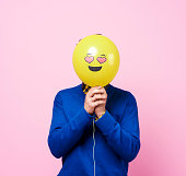 In love man hiding behind balloon