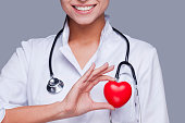 Close-up of female doctor in white uniform holding heart prop and smiling