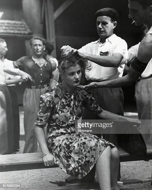 In Montelimar France French civilians shave the head of a young woman as punishment for her involvement with the Germans during World War II