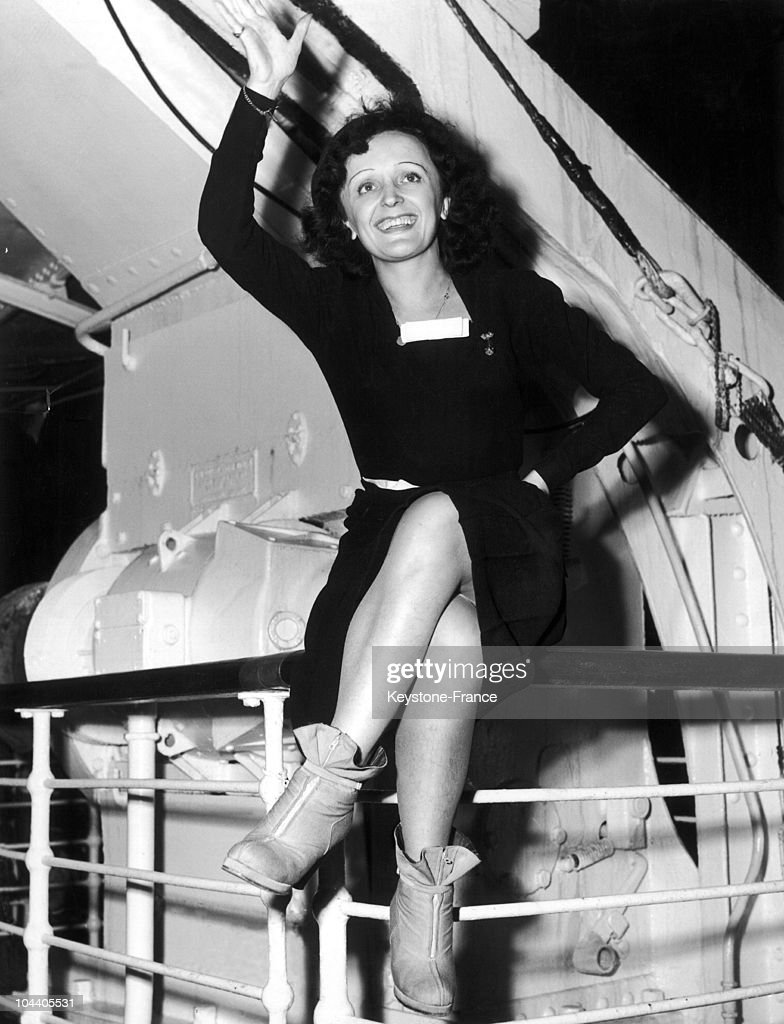 In October-November 1947, upon her arrival in New York for her United States tour, the popular singer Edith PIAF greets the crowd while sitting on the rail of the transatlantic ship the QUEEN