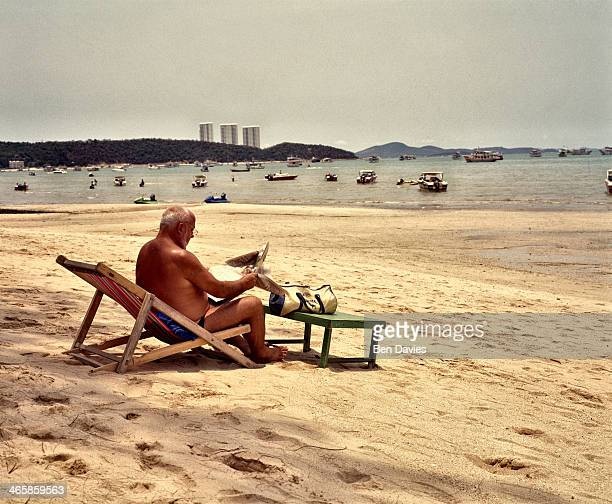 In Pattaya one of Thailand's most infamous beach resorts on the Gulf of Thailand a tourist sits out on a deck chair staring out over the bay crowded...