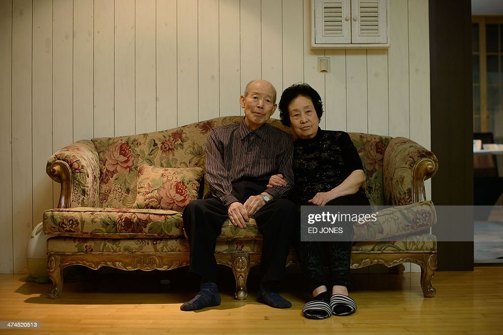 In photo taken on February 22, 2014 Kim Se-Rin (L) poses for a photo with his wife at his home in Seoul after returning from a family reunion with his North Korean relatives. Among tens of thousands of wait-listed applicants, the 85-year-old was one of just 83 South Koreans chosen to participate in a meeting of family members divided by the 1950-53 Korean War. Kim left his hometown in the North Korean county of Hwangju in December 1950 at the height of the war to join the South Korean army, without telling his parents, his brother or his two sisters. In the six decades since, he had no contact with those he left behind, not knowing whether they were alive or dead. Millions of Koreans were separated by the conflict and permanent division of the peninsula. The joy of reunion is tempered by the pain of the inevitable -- and permanent -- separation at the end. Although he knew it would be near impossible to expect answers to more than 60 years worth of questions, Kim was grateful to have finally heard how his parents died and how his other relatives lived during the years since he left. Of the 125,000 South Koreans who have applied for reunions since 1988, 57,000 have died with time rapidly running out for those on the wait list. AFP PHOTO / Ed Jones