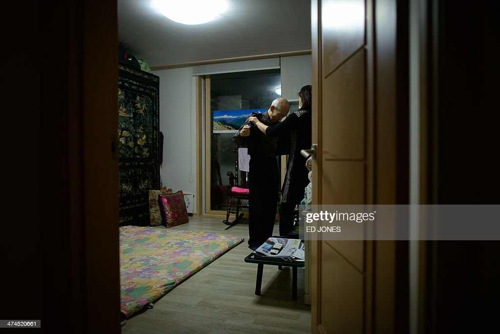 In photo taken on February 22, 2014 Kim Se-Rin (C) takes off his jacket with help from his daughter Kim Young-Soon in his bedroom at his home in Seoul after returning from a family reunion with his North Korean relatives. Among tens of thousands of wait-listed applicants, the 85-year-old was one of just 83 South Koreans chosen to participate in a meeting of family members divided by the 1950-53 Korean War. Kim left his hometown in the North Korean county of Hwangju in December 1950 at the height of the war to join the South Korean army, without telling his parents, his brother or his two sisters. In the six decades since, he had no contact with those he left behind, not knowing whether they were alive or dead. Millions of Koreans were separated by the conflict and permanent division of the peninsula. The joy of reunion is tempered by the pain of the inevitable -- and permanent -- separation at the end. Although he knew it would be near impossible to expect answers to more than 60 years worth of questions, Kim was grateful to have finally heard how his parents died and how his other relatives lived during the years since he left. Of the 125,000 South Koreans who have applied for reunions since 1988, 57,000 have died with time rapidly running out for those on the wait list. AFP PHOTO / Ed Jones