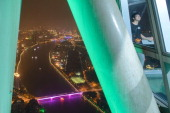 In photo taken on November 11 2013 a man has his photo taken at a viewing booth atop the Canton Tower before the skyline of the southern Chinese city...
