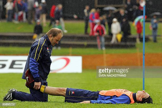In pouring rain Swedish striker Zlatan Ibrahimovic gets a stretch treatment after the national team practice in Gimo 25 May 2004 where the preEURO...