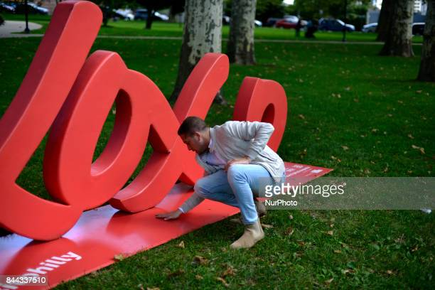 In preparation for the Parkway100 centennial celebration Jorden Parenti with Visit Philly inspects a xoxo sculpture alongside the Benjamin Franklin...
