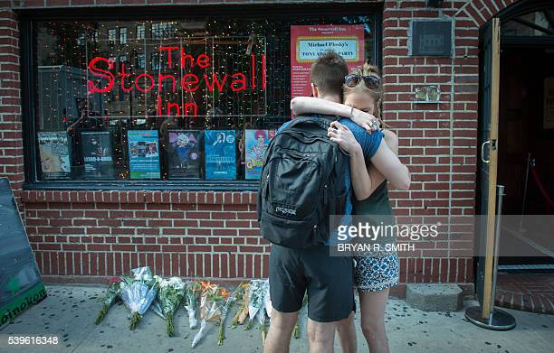 In reaction to the mass shooting at a gay nightclub in Orlando Florida people hug outside the Stonewall Inn near a vigil for the victims in New York...