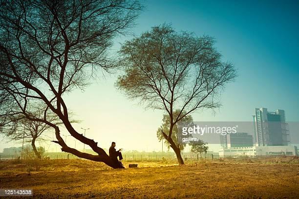 In rural landscape businessman sitting far from city under tree