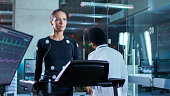 In Scientific Sports Laboratory Beautiful Woman Athlete Walks on a Treadmill with Electrodes Attached to Her Body, While Black Scientist Going Away, Monitors Show EKG Data on Display.