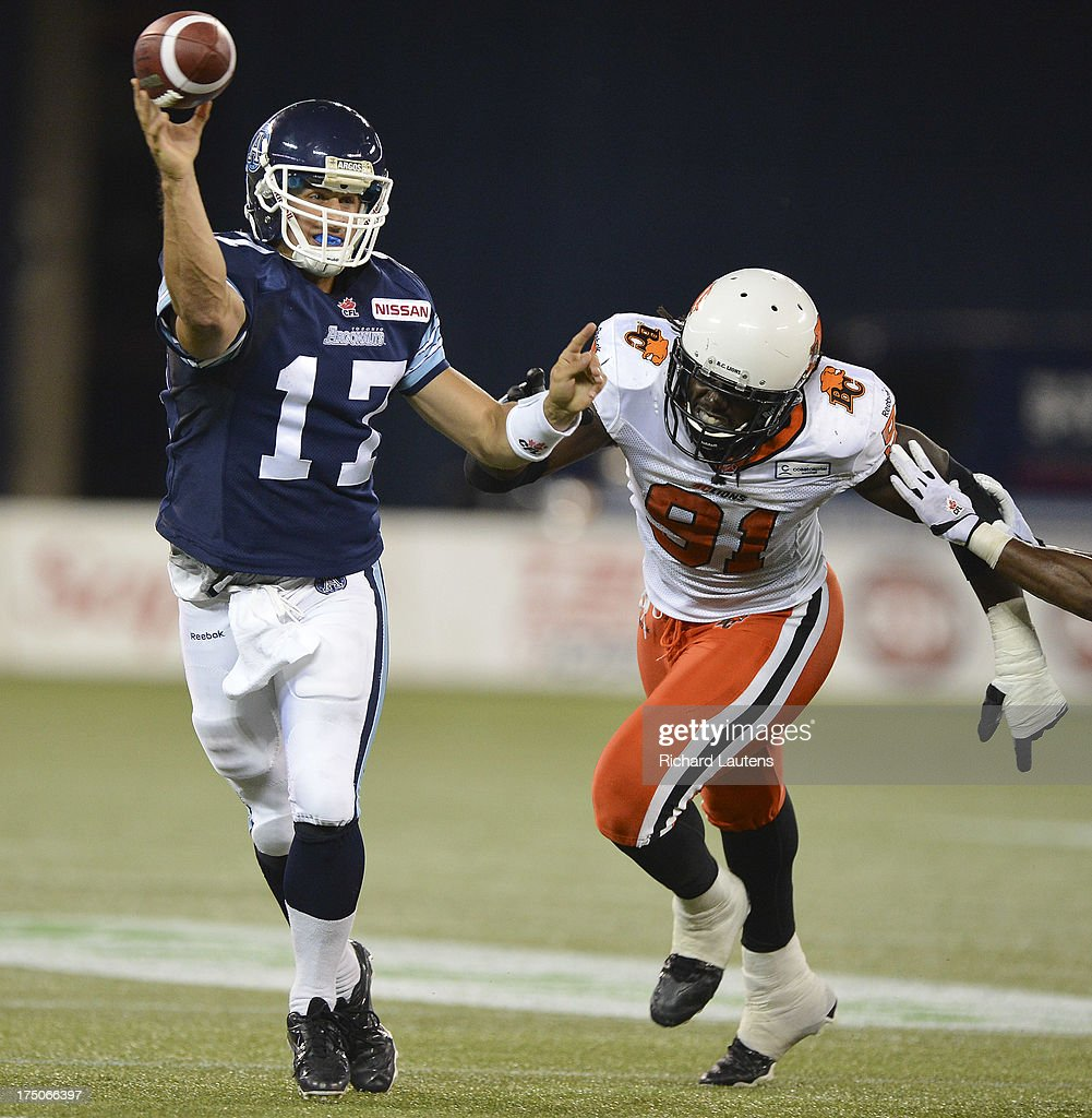 TORONTO, ON - JULY 30 - In second half action, Argo QB Zach Collaros throws under pressure from BC's Brandon Jordan. The Toronto Argonauts beat the BC Lions 38-12 at the Rogers Centre in Toronto. The Argos were without their starting quarter back and running back. July 30, 2013.