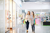 Young women with paper bags walking in the mall