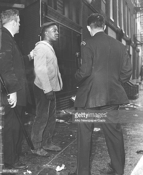 In the aftermath of a riot police officers one with a billy club and other with a shotgun arrest a unidentified man at Franklin and Gilmor streets...