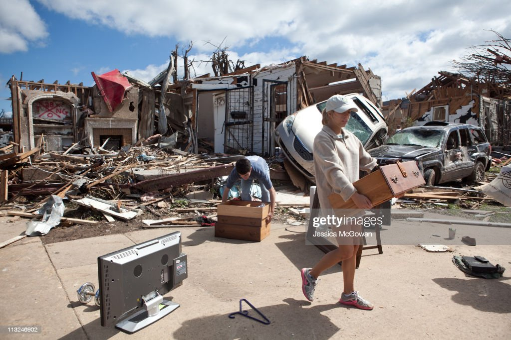 In the aftermath of a severe tornado, Kelly Giddens (R) helps University of Alabama law student Daniel Hinton remove belongings from his destroyed home in the Cedar Crest neighborhood on April 28, 2011 in Tuscaloosa, Alabama. As of 8 a.m., at least 131 deaths were accounted for in Alabama. The tornado that touchdown in Tuscaloosa is estimated to be one mile wide.