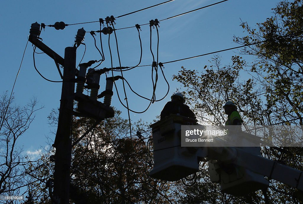 In the aftermath of Superstorm Sandy, an electrical work crew from Arizona works on overhead lines on Quaker Path Road on November 4, 2012 in Stony Brook, New York. With the death toll currently over 100 and millions of homes and businesses without power, the U.S. East Coast is attempting to recover from the effects of floods, fires and power outages brought on by Superstorm Sandy.