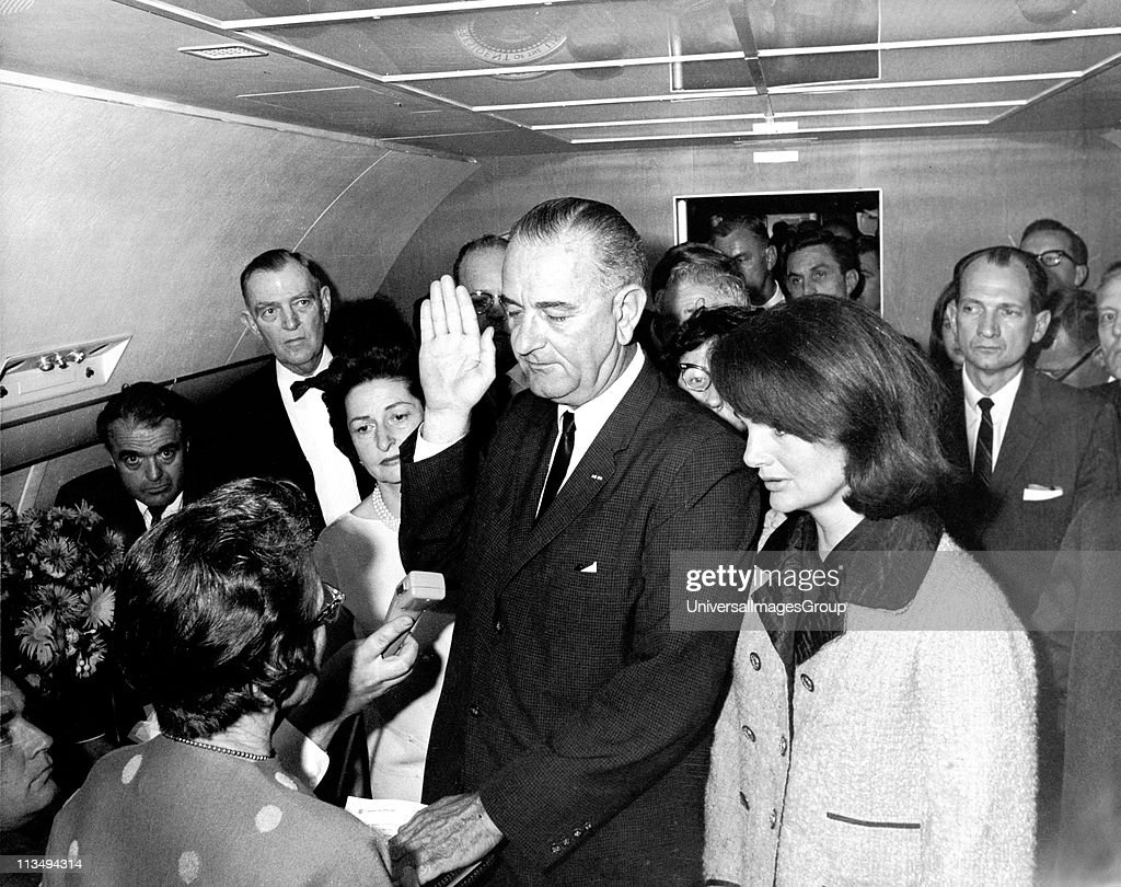 In the aftermath of the assasination of US President John F. Kennedy, American politician and Vice-President Lyndon Baines Johnson (1908 - 1973) takes the oath of office to become the 36th President of the United States as he is sworn in by US Federal Judge Sarah T. Hughes (1896 - 1985) (left) on the presidential aircraft, Air Force One, Dallas, Texas, November 22, 1963. Kennedy's widow, Jacqueline Lee Bouvier Kennedy (later Onassis) stands beside him at right.