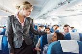 Smiling flight attendant talking to female passenger.