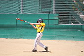 Taking a few swings before stepping to the plate in a little league game.