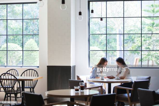 In the bright sunshine, two college girls spend in a beautiful restaurant.