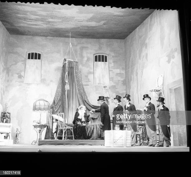 In the centre of the stage sat down on a bed the mad Aurelia is being visited by five elegantly dressed men Piccolo Teatro Milan February 24 1954