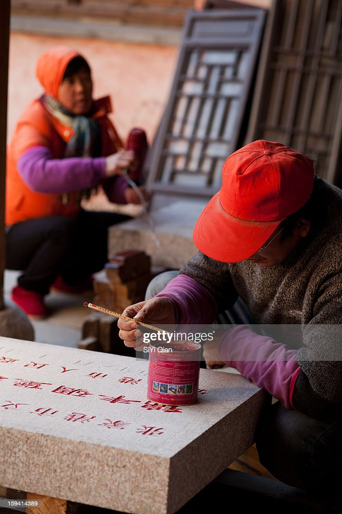 CONTENT] In the Confucian Temple locating in the east of China, the man working on restoration of cultural relics is repairing inscription in red brush