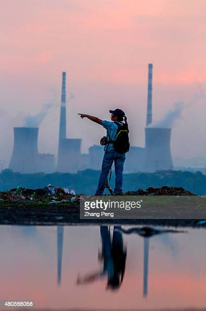 In the dusk a young girl stands beside Haizhou opencast coal mine the opposite is a thermal power plant which had also been the largest in Asia Both...