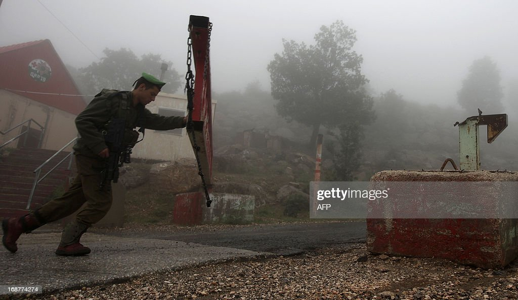 In the early morning fog, an Israeli soldier partially closes a barrier across a road, on Mount Hermon in the northern Israel occupied Golan Heights on May 15, 2013, after two projectiles fired from Syria hit Mount Hermon without causing damage or injuries, an Israeli army spokeswoman told AFP. Israel, which is technically at war with Syria, seized 1,200 square kilometres (460 square miles) of the strategic Golan Heights during the 1967 Six-Day War, which it later annexed in a move never recognised by the international community. AFP PHOTO/ JALAA MAREY