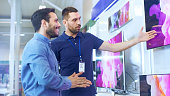 In the Electronics Store Professional Consultant Shows Latest 4K UHD TV's to a Young Man, They Talk about Specifications and What Model is Best for Young Man's Home. Store is Bright, Modern and Has al
