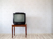 In the empty room, the old tube TV on the coffee table
