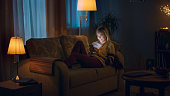 In the Evening Beautiful Young Woman Lies on the Couch and Uses Smartphone. Room Looks Warm and Cozy.