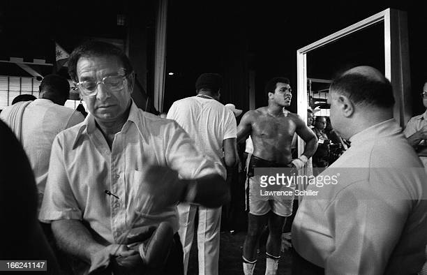 In the foreground American boxing cornerman and trainer Angelo Dundee works on a glove while in the background boxer Muhammad Ali stands with his...