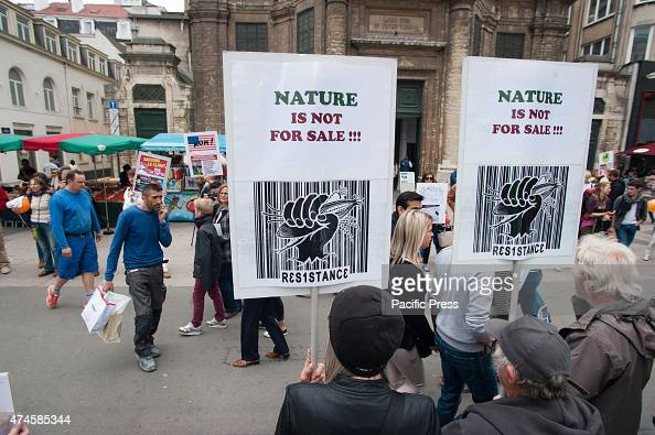 In the foreground protesters are seen holding a sign that says 'nature is not for sale' with a bar code with in the background a busy shopping street...