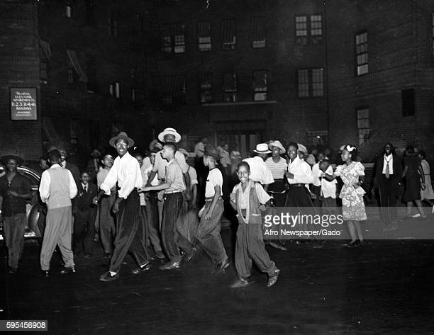 In the Harlem neighborhood of Baltimore Maryland a group of AfricanAmerican youth smile and walk down the street just prior to the start of a riot...