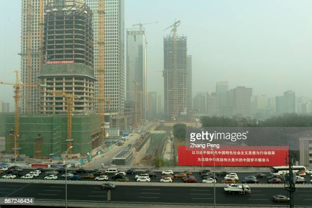 In the heavy haze Huge red propaganda poster is very striking beside the construction site of China Zun at Beijing CBD which is about Chairman Xi's...