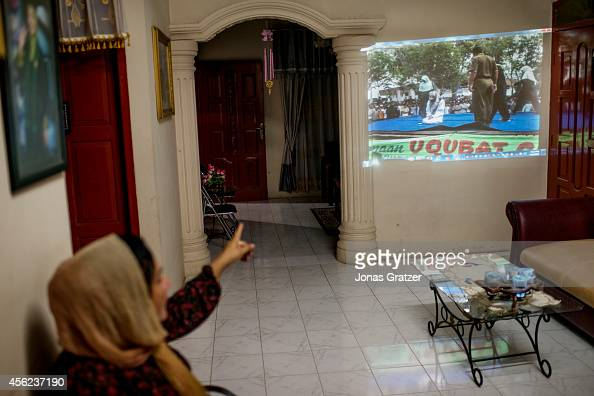 In the home of the Chief in Justice of the region's Sharia Court Dr Rafiuddin shows a projected video to his family of a woman who is punished for...