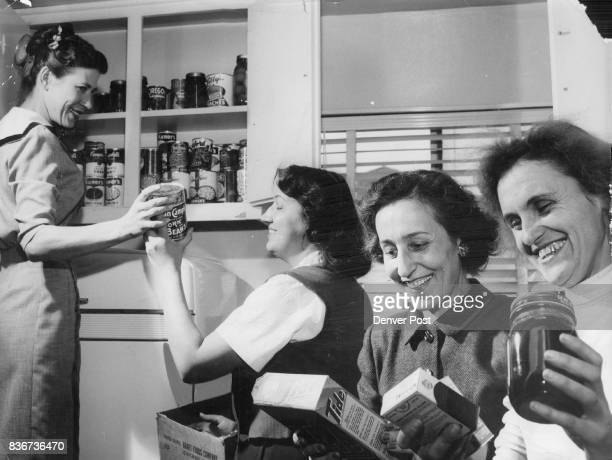In the kitchen putting away food for Denver's new Josef Holubecz refugee family are Mrs Edward Duggan 1166 Rosemary St Mrs Louis Igo 2784 W Dunkeld...