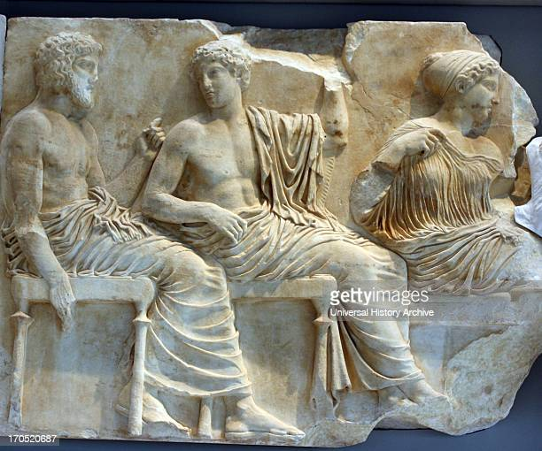 In the left section of the scene Poseidon holding a trident and Apollo holding a laurel branch with the other beside them sit two sister divinities...
