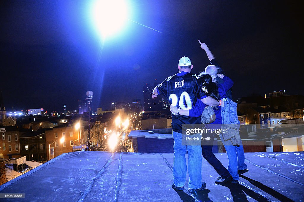 In the light of a Baltimore City police helicopter light, employees of Mother's Federal Hill Grille (L-R), JoJo Wiley, Lindsey Goforth and Joe Goforth, celebrate as Baltimore Ravens cheer in the streets after Super Bowl XLVII against the San Francisco 49ers in the neighborhood of Federal Hill on February 3, 2013 in Baltimore, Maryland. The Baltimore Ravens won the Super Bowl, 34-31, to capture their second championship title.