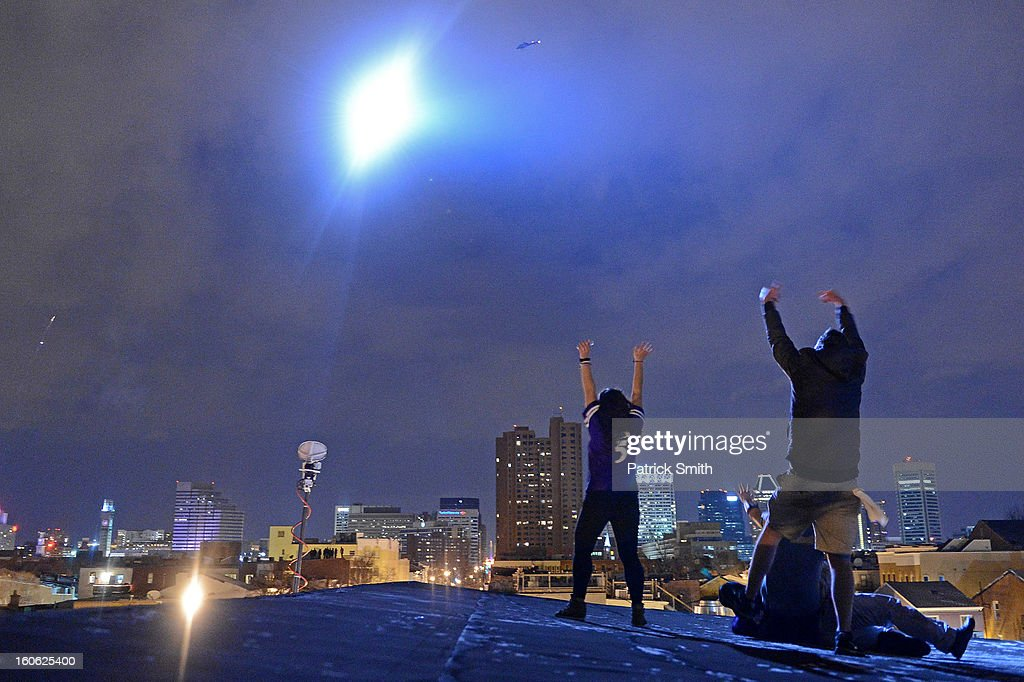 In the light of a Baltimore City police helicopter light, employees of Mother's Federal Hill Grille celebrate as Baltimore Ravens cheer in the streets after Super Bowl XLVII against the San Francisco 49ers in the neighborhood of Federal Hill on February 3, 2013 in Baltimore, Maryland. The Baltimore Ravens won the Super Bowl, 34-31, to capture their second championship title.