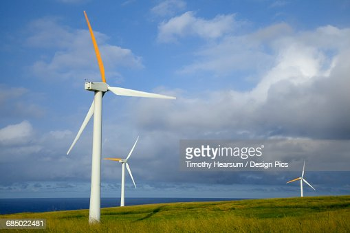 In the North Kohala District of the Big Island, three wind generators overlook the Pacific Ocean, with clouds and blue sky in the background : Stock Photo