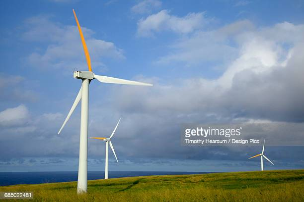 In the North Kohala District of the Big Island, three wind generators overlook the Pacific Ocean, with clouds and blue sky in the background