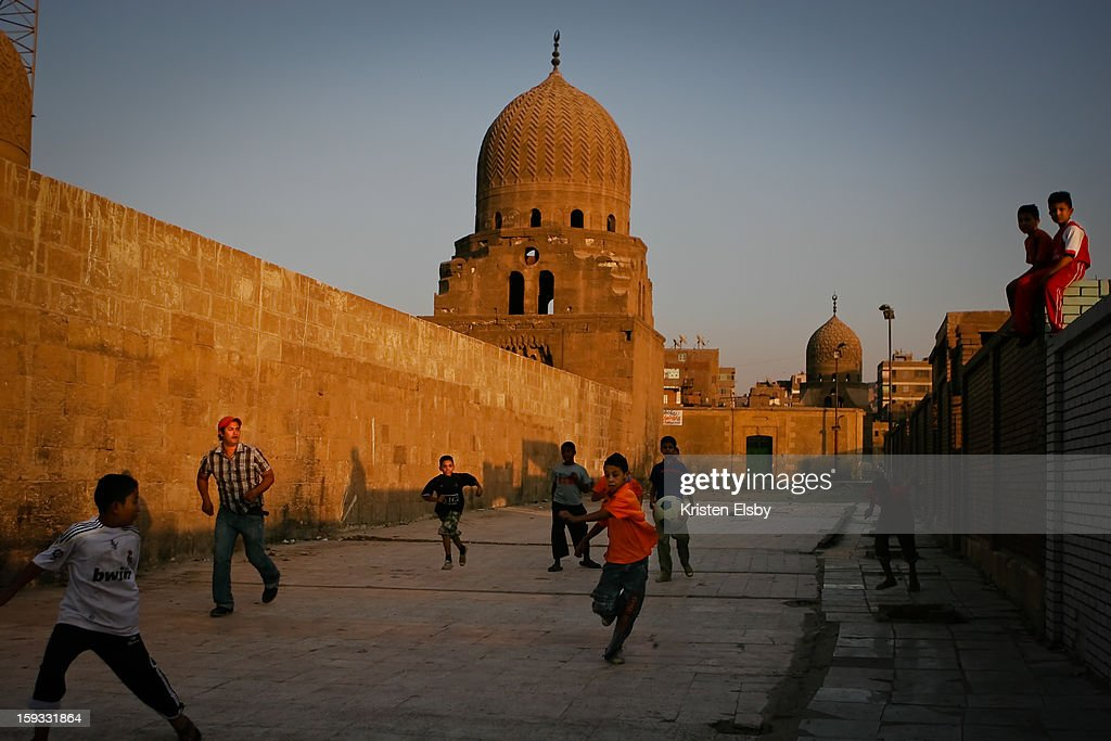 CONTENT] In the northern part of old Cairo, it is said that between 50,000 and 1,000,000 million people live amongst the tombs in Qarafa Cemetery, also known as the City of the Dead. These boys live with their families in the cemetery, spending afternoons playing soccer in the alleys beyond the tombs.