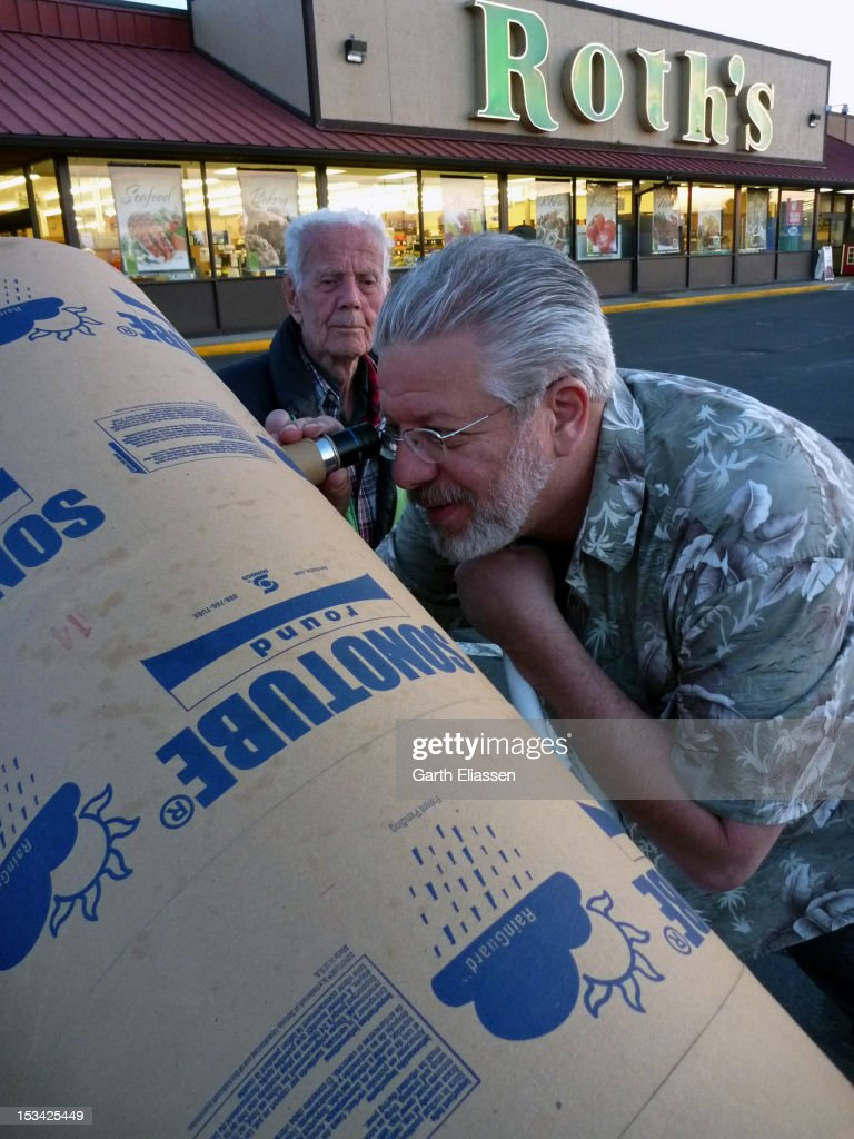 In the parking lot of Roth's market, American astronomer and telescope-maker John Dobson (left) watches as mirror-maker Carl Zambuto (of the Zambuto Optical Company) looks through one of his home-made telescopes, Independence, Oregon, July 9, 2011. The Dobsonian telescope, a type of Newtonian telescope on a cannon mount, helped to revolutionize amateur astronomy, making it possible for large-aperture telescopes to be home-made with readily-available materials.