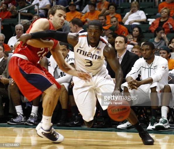 In the second half Miami's Malcolm Grant right drives to the basket against Pablo Bertone of Florida Atlantic in the first round of the NIT...