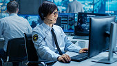 In the Security Command Center Officer at His Workstation Monitors Screens and Communicates with Patrols through Headset. He is Part of the Surveillance Team.