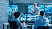 In the Security Control Room Chief Surveillance Officer Holds a Briefing for Two of His Subordinates. Multiple Screens Show that They Guard Object of International Importance.