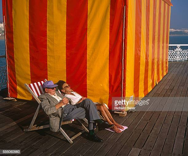 In the shelter of a large red and yellowstriped marquee tent a middleaged husband and wife relax in deck chairs on Brighton's East Pier England The...